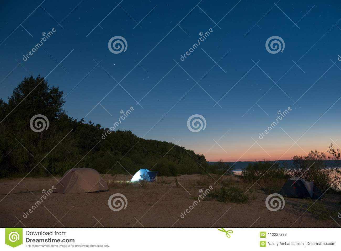 tourist tents on a sandy beach at night with moonlight surrounded by
