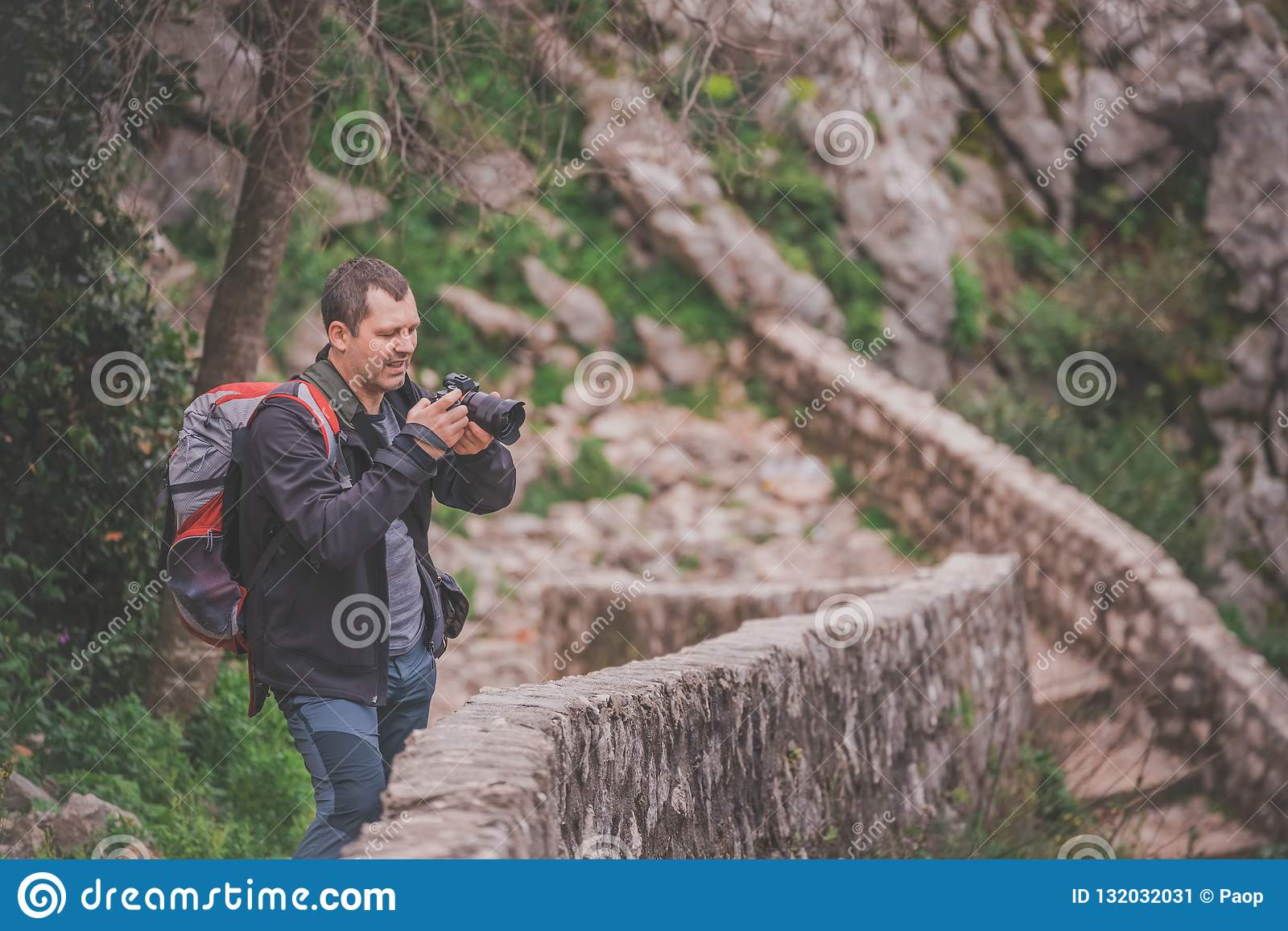 Tourist on a trail checking images on camera