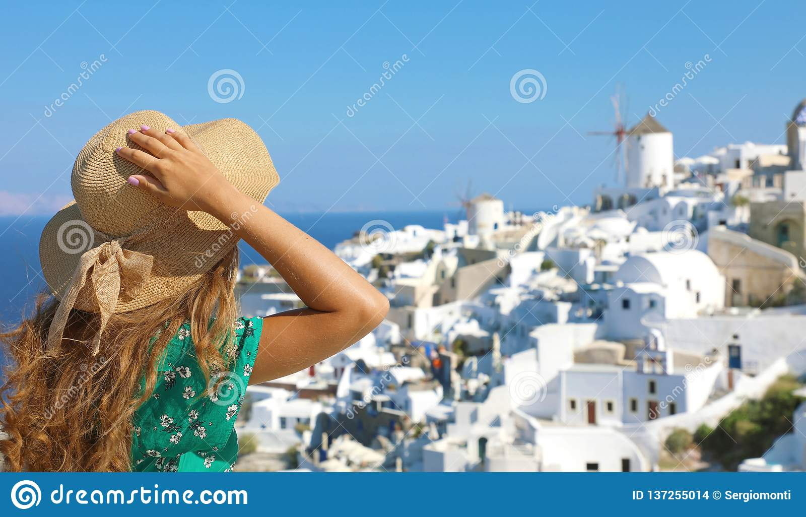Tourist traveling in Santorini, Oia island in Greece, Europe travel summer vacation woman relaxing at view windmills. Holiday girl