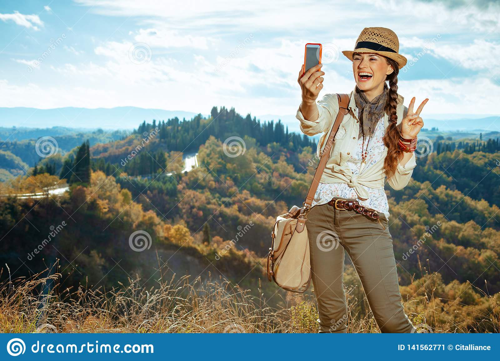 Tourist woman taking selfie with phone and showing victory