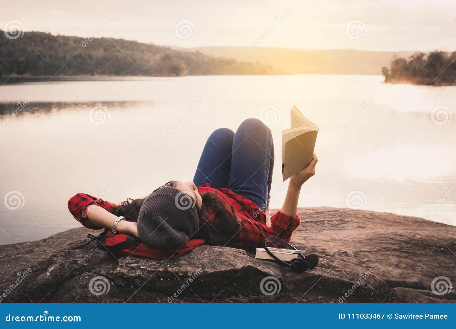Touriste asiatique de détente de moment lisant un livre sur la roche