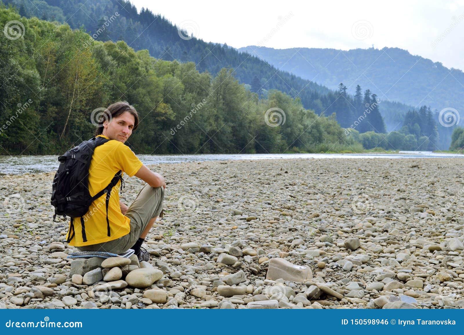 Touriste d homme dans le T-shirt jaune avec un sac à dos se reposant sur les roches sur la rivière sèche, en montagnes de fond et