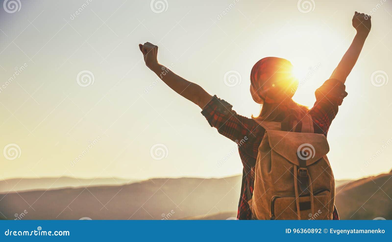 Touriste de femme au sommet de montagne au coucher du soleil dehors pendant la hausse