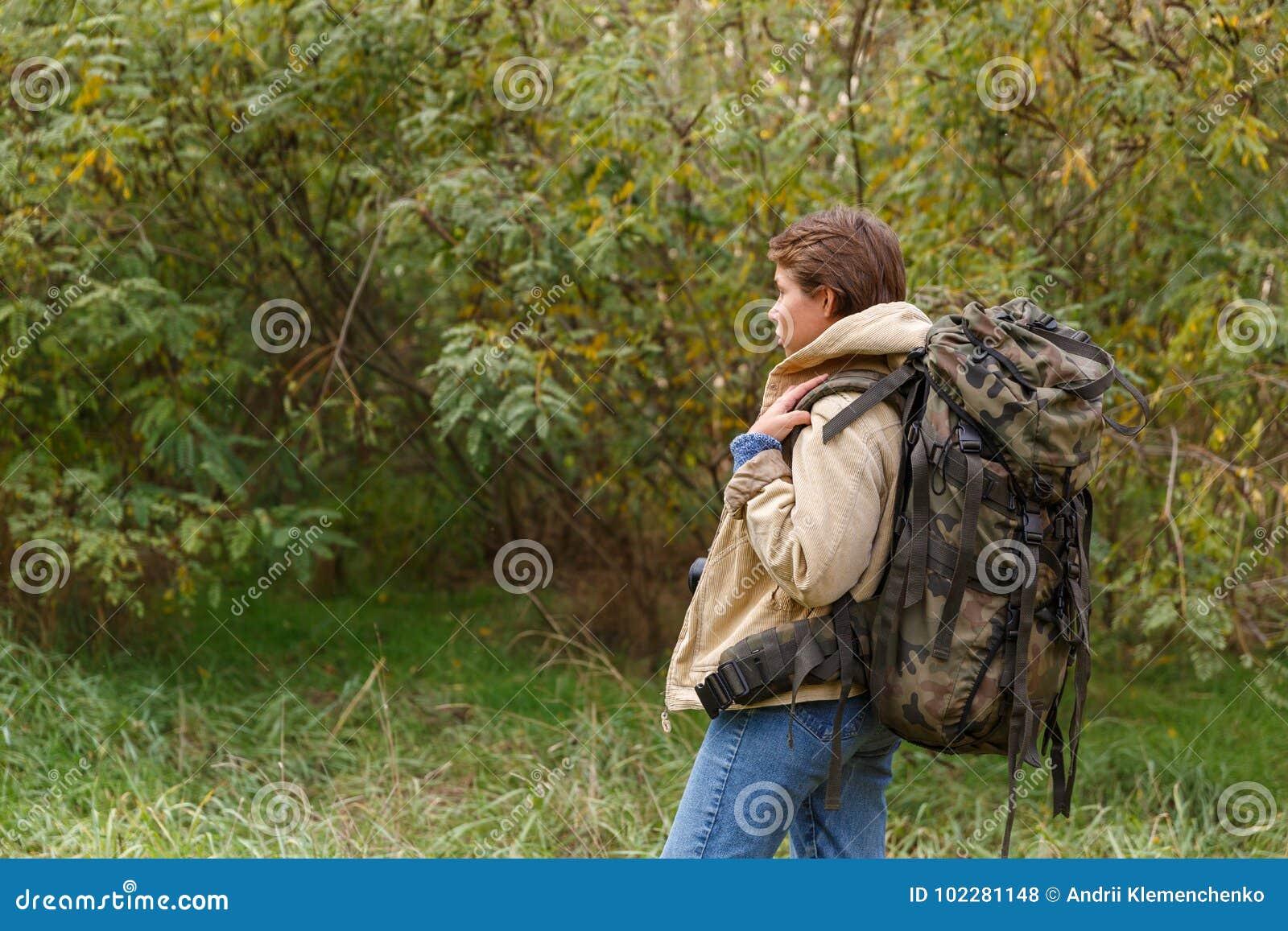 Touriste de jeune fille, marchant par une forêt avec un grand sac à dos sur elle de retour