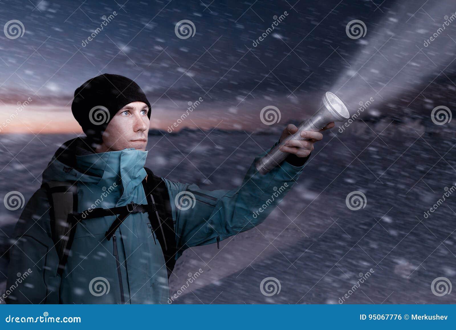 Touriste de montagne avec une lanterne à disposition allumant la manière dans l obscurité de la nuit