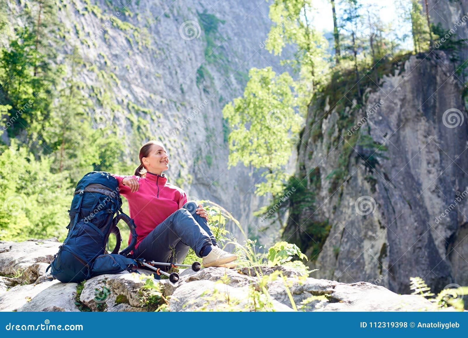 Touriste féminin de sourire se reposant sur la beauté admirative de roche des montagnes rocheuses stupéfiantes dans l endroit spe