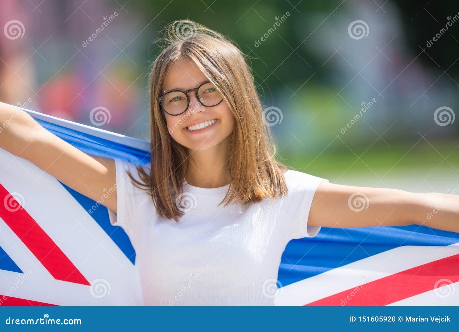 Touriste heureux de fille marchant dans la rue avec le drapeau de la Grande-Bretagne