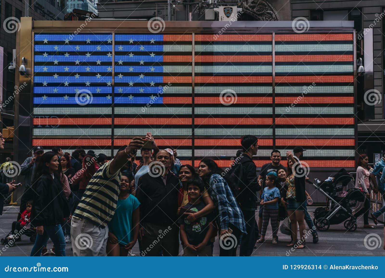 Touristen, die selfies herein von auf einer großen geführten amerikanischen Flagge im Ti nehmen