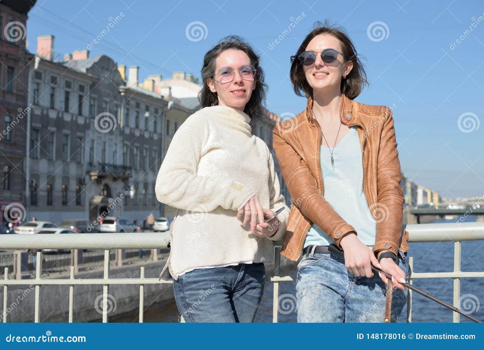 Touristes de jeunes dames dans le St Petersbourg Russie prendre des selfies sur un pont en bois au centre de la ville historique