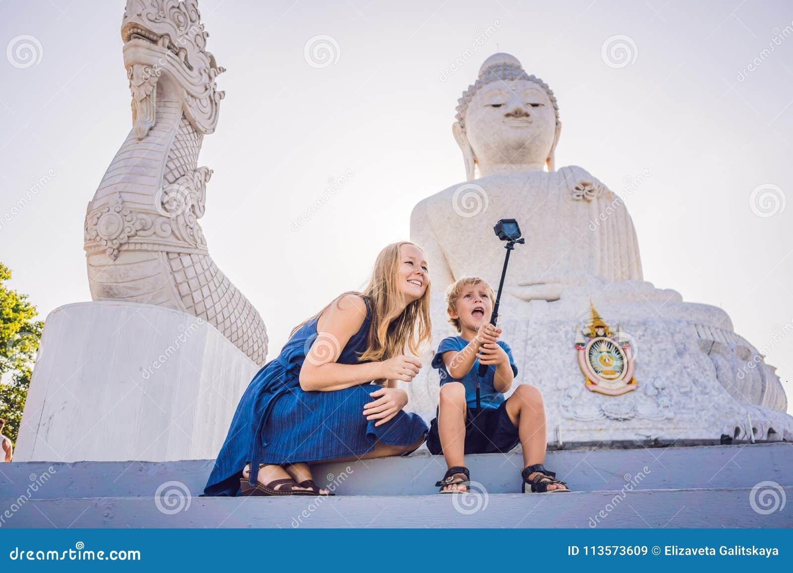 Touristes de mère et de fils sur la grande statue de Bouddha A été construit sur un sommet élevé de Phuket Thaïlande peut être vu
