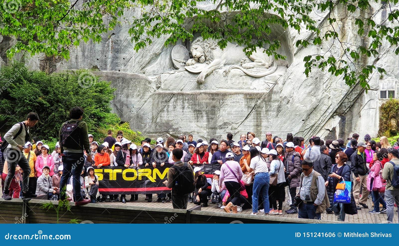 Touristes de masse prenant une photo de groupe devant le monument de lion, luzerne Suisse