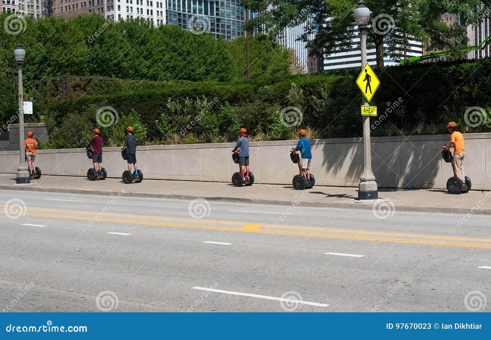 Touristes sur des seagways montant par une rue de Chicago
