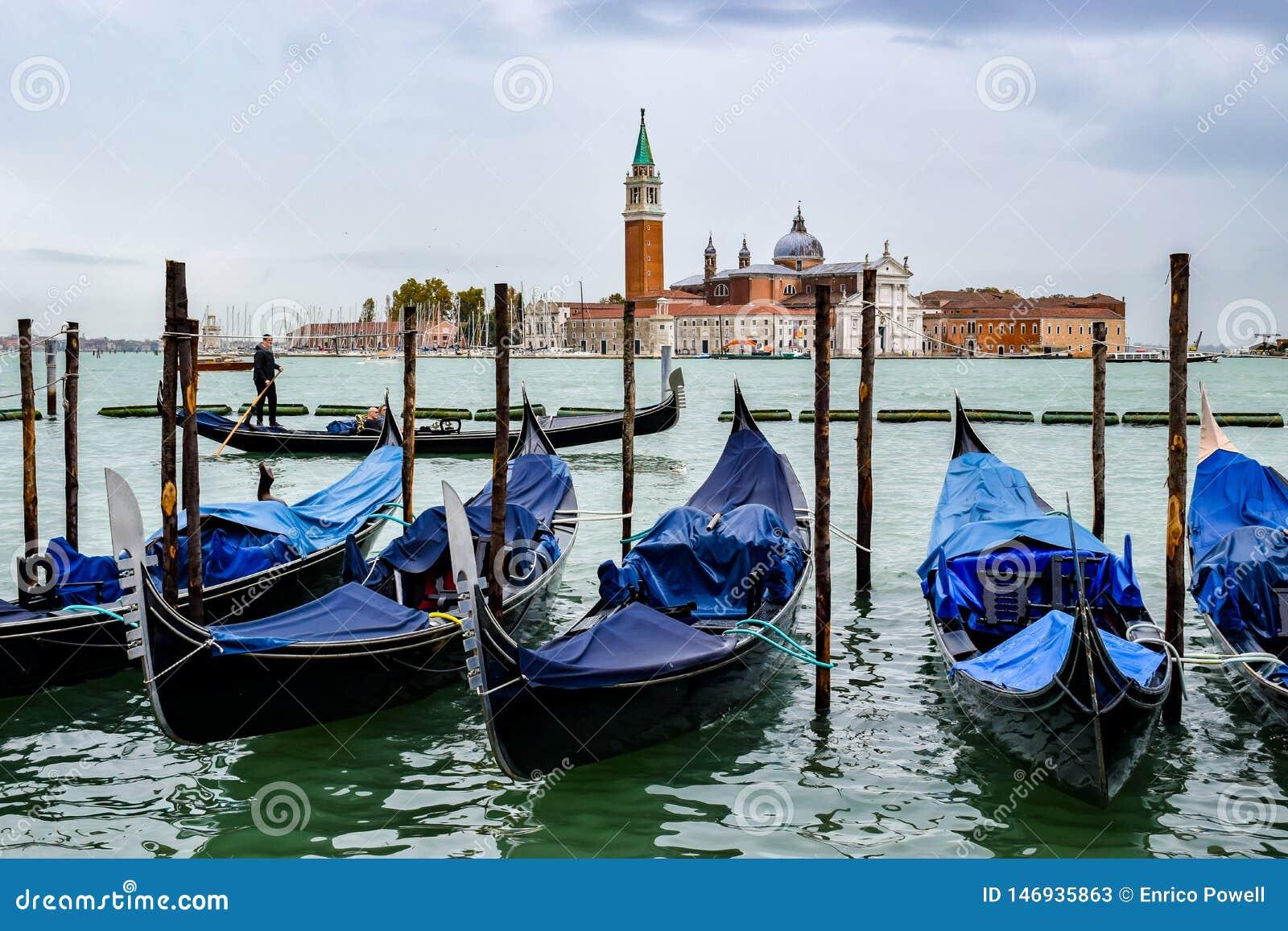 Touristes sur le tour de bateau de gondole entre les gondoles et l église accouplées vides de San Giorgio Maggiore à l arrière-pl