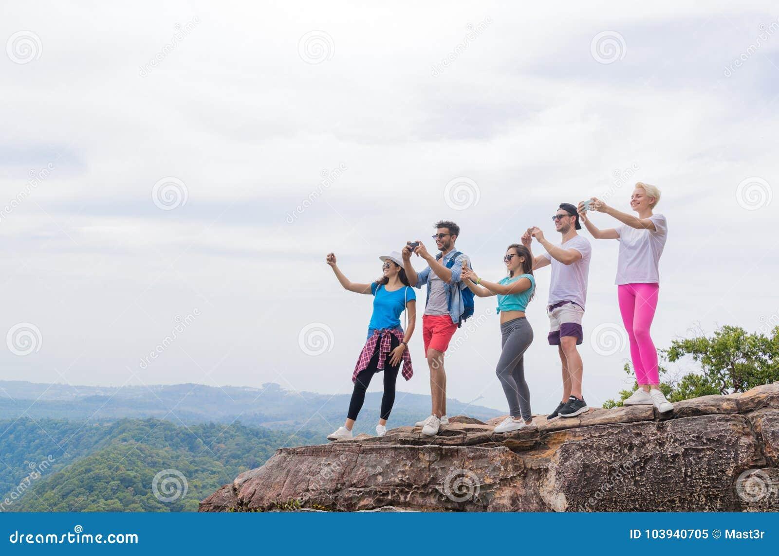 Touristische Gruppe mit Rucksack machen Foto der Landschaft von der Gebirgs-Spitze an Zell-Smart-Telefon
