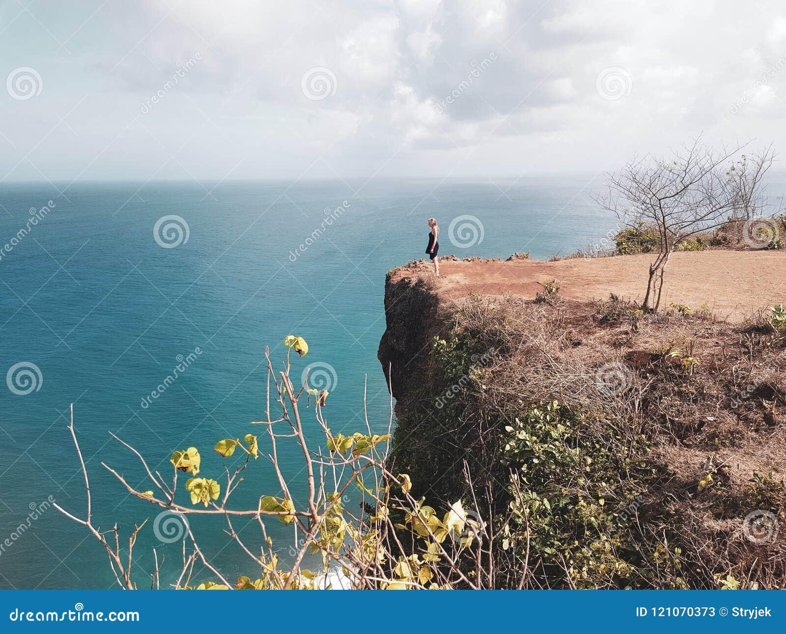 Touristische Stellung des Mädchens auf der Klippe