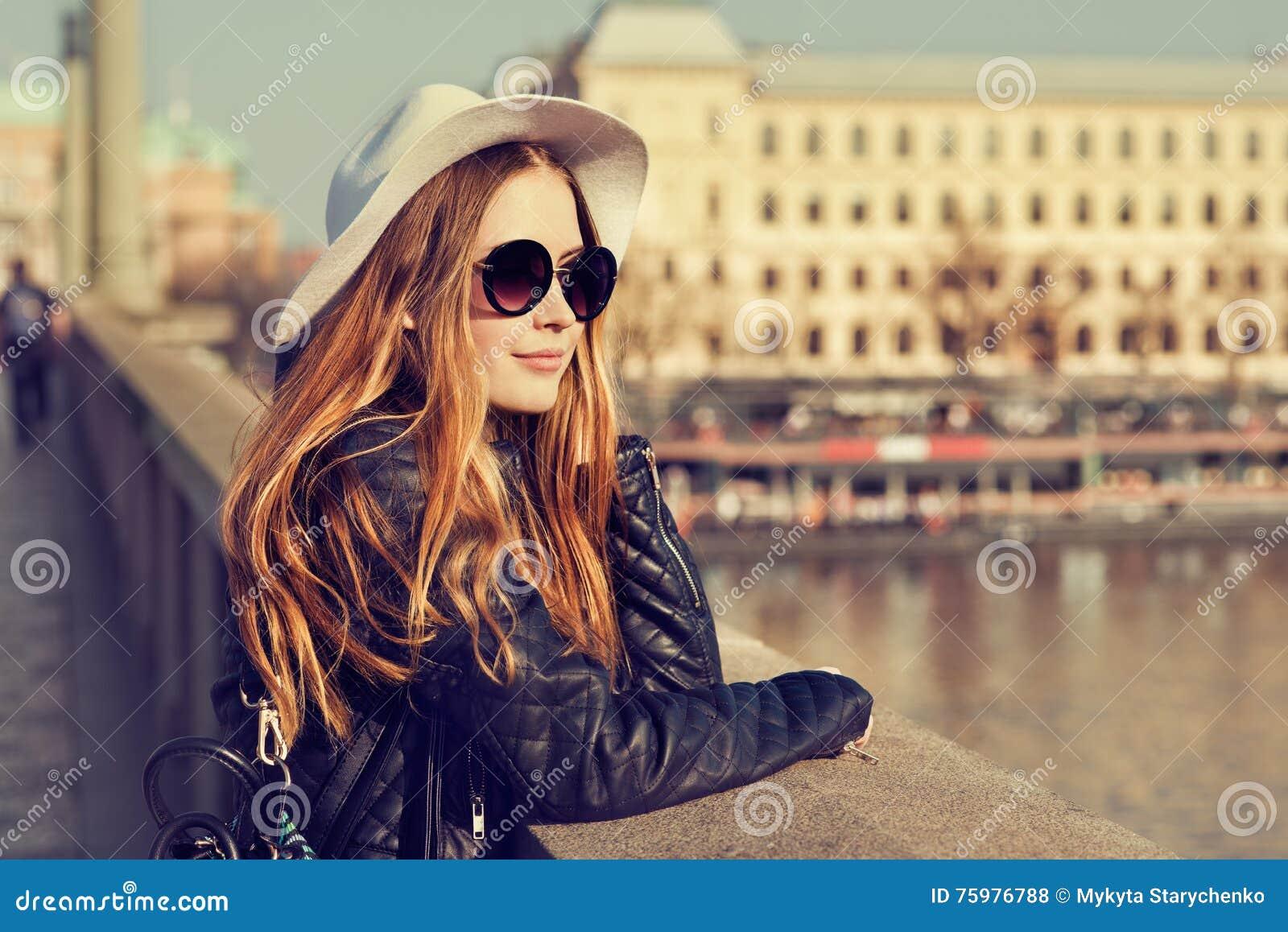 Touristisches nettes Mädchen des jungen hübschen Hippies, das auf der Straße am sonnigen Tag aufwirft und um europäische Stadt re