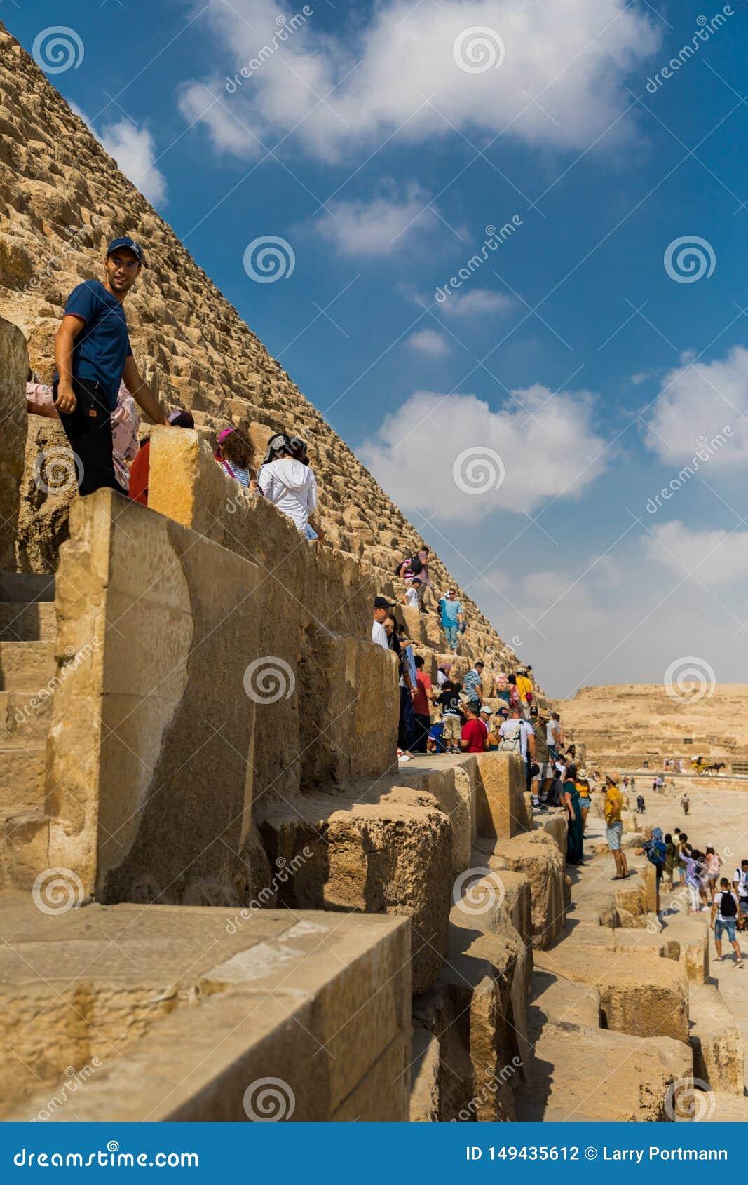 Tourists climbing the pyramids of Giza, Egypt