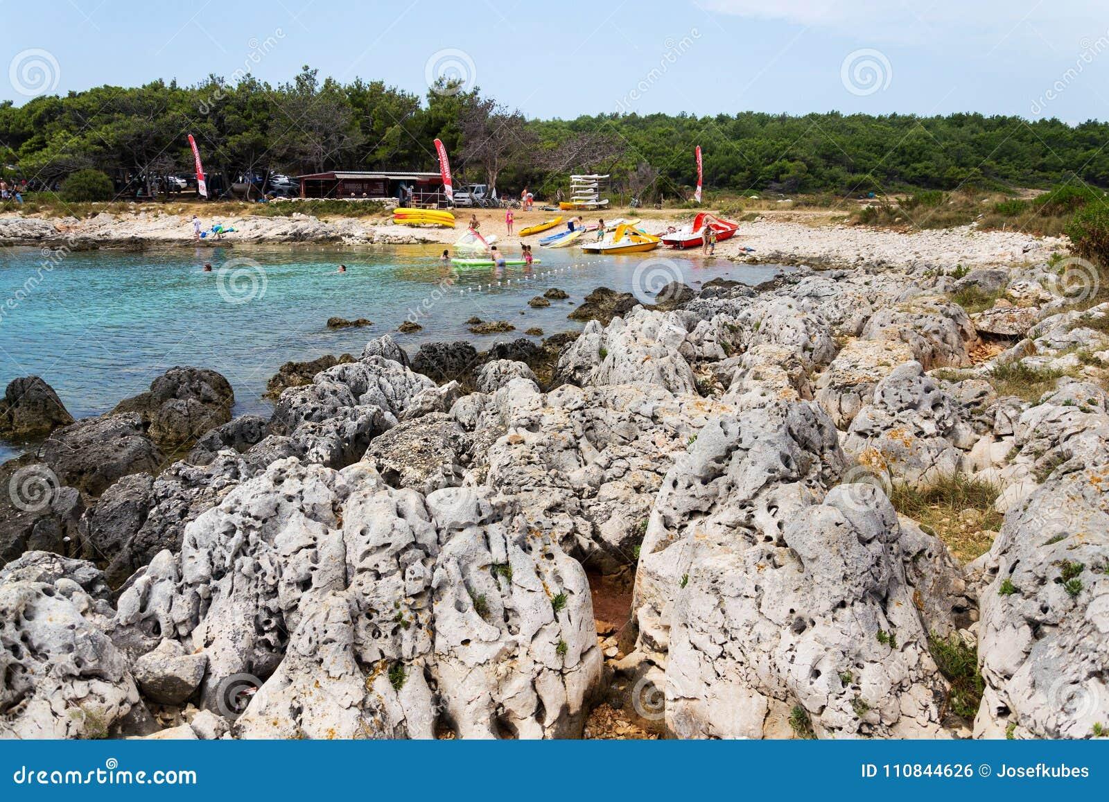 Tourists on Kamenjak peninsula beach by the Adriatic Sea in Premantura, Croatia