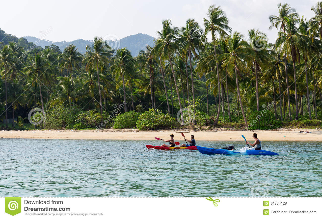 Tourists kayaking on sunny tropical beach with palm trees for Warm vacations in march