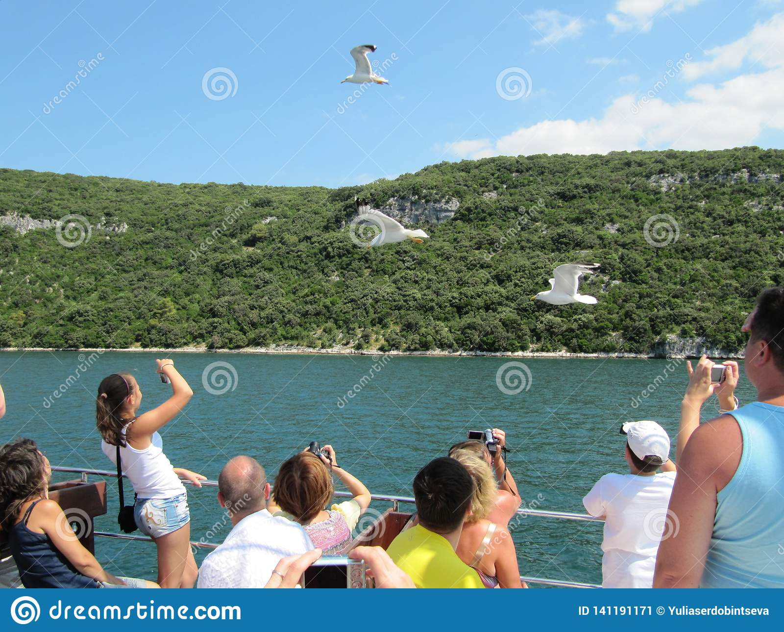 Tourists sailing on the ferry to feed seagulls and take pictures. Croatia, Istra - July 20, 2010.