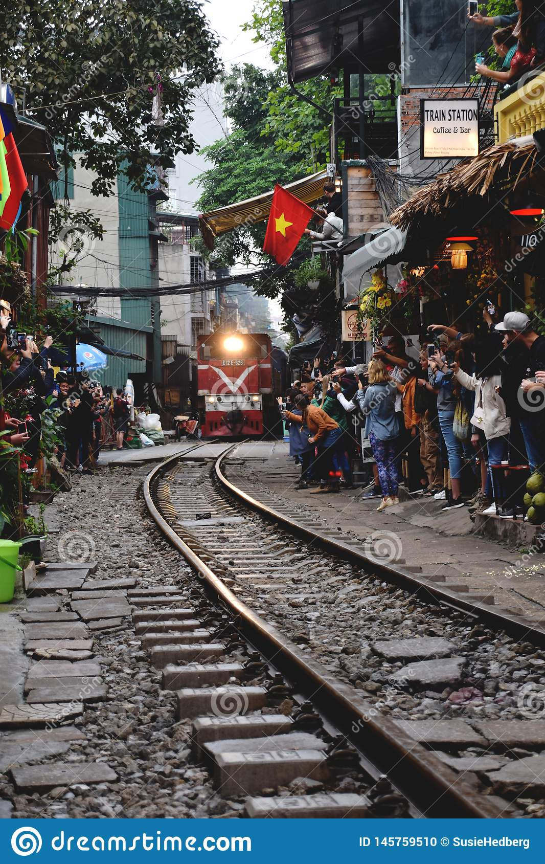 Tourists taking photo of train on tracks running very narrow to houses in Hanoi