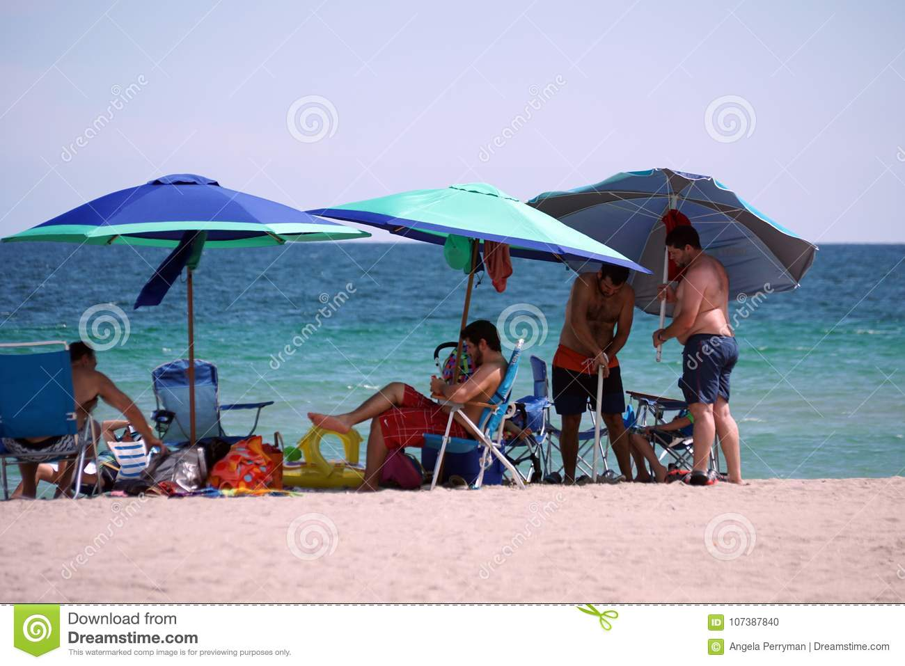 Tourists In Lounge Chairs Under Colorful Beach Umbrellas With The Atlantic  Ocean In The Background On Dania Beach, Fort Lauderdale, Florida, USA
