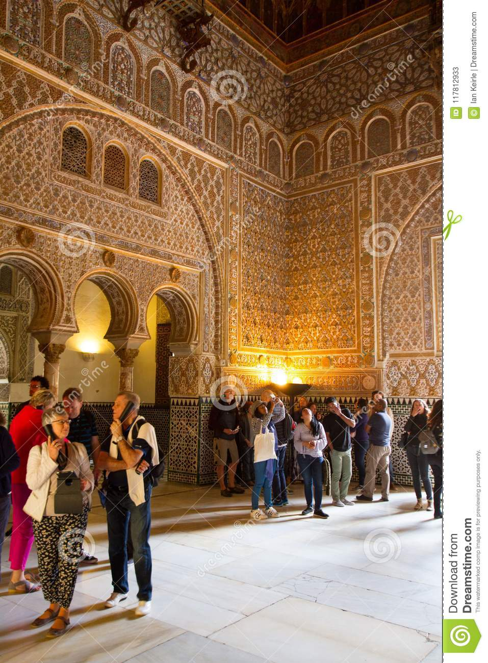 tourists viewing the islamic architecture of the alcazar in seville