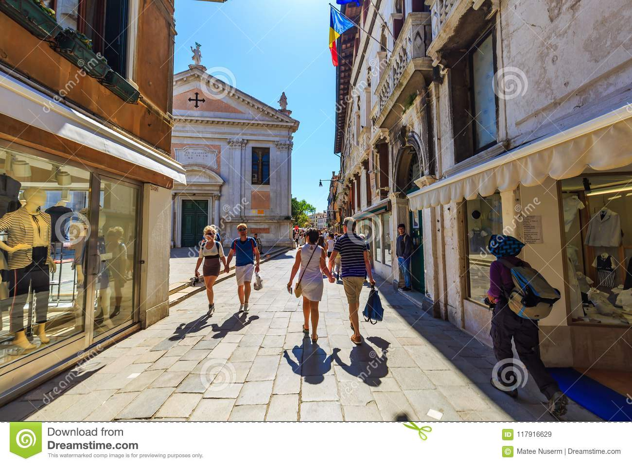 Tourists walk along the street in Venice