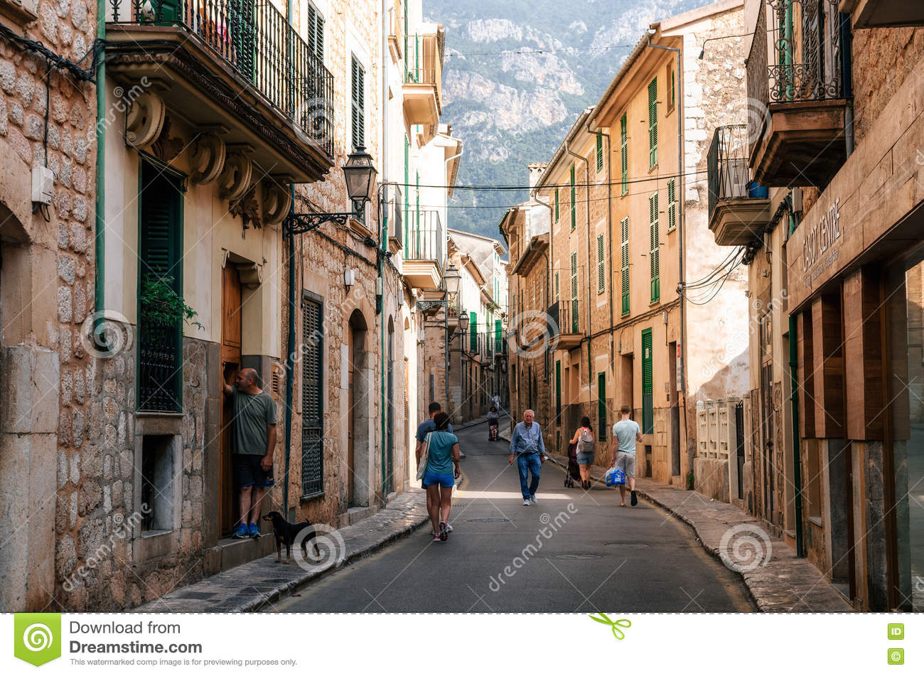 Tourists walking along at historical town part of Soller with its traditional house
