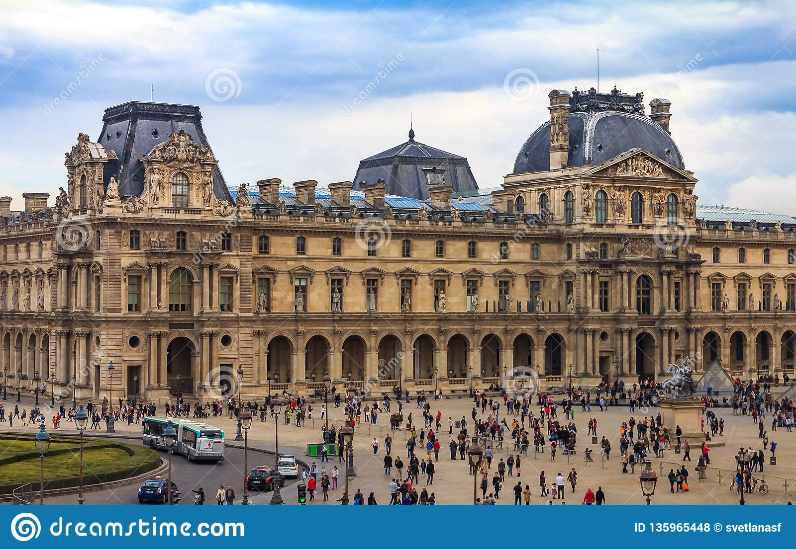 Tourists Walking In Front Of The Famous Louvre Museum One