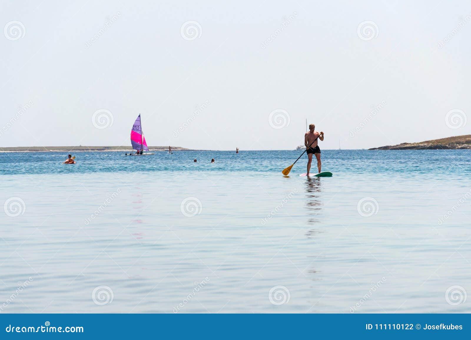 Tourists windsurfing and paddleboarding around Kamenjak peninsula by the Adriatic Sea in Premantura, Croatia