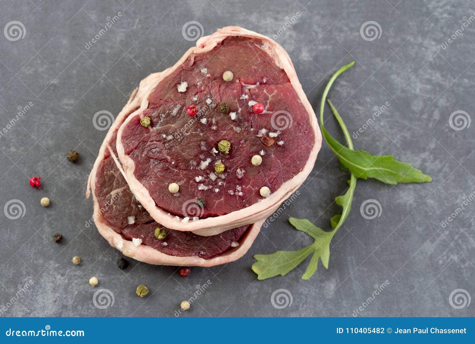 Tournedos: een kleine ronde dikke besnoeiing van een filet van achtergrond van de rundvlees de grijze lei boven mening