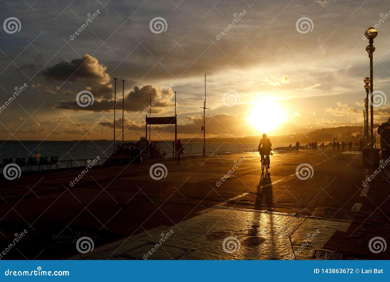 Tours de cycliste le long de la promenade contre le ciel de coucher du soleil
