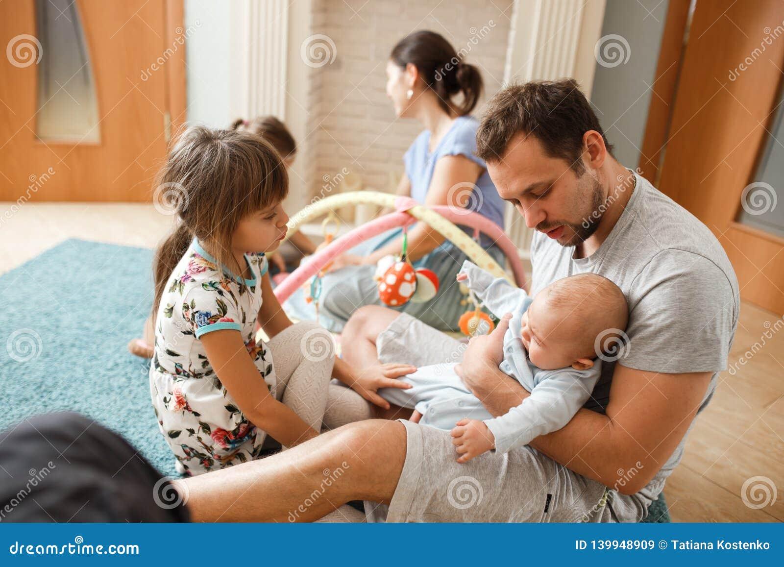 Tout le père de famille, mère, deux filles et peu de fils de bébé passant le temps sur le tapis dans la chambre