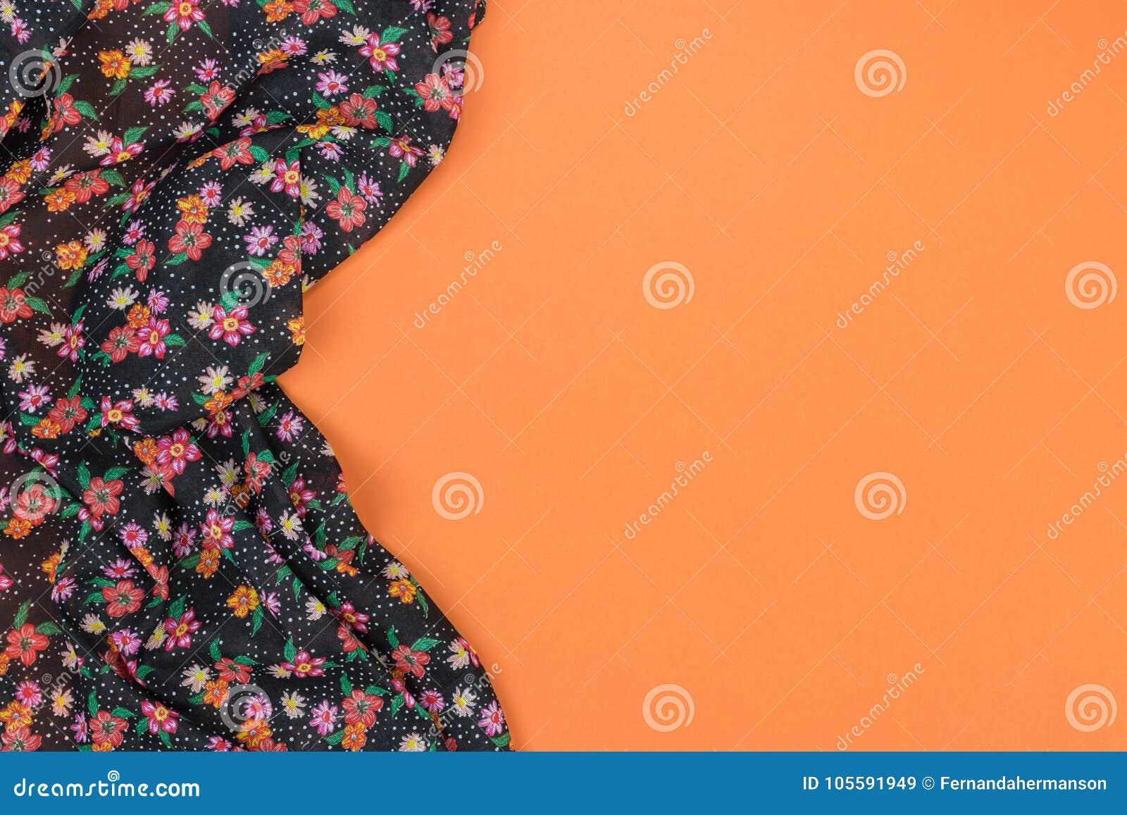 Tovaglia floreale del modello su fondo arancio vuoto Vista superiore w