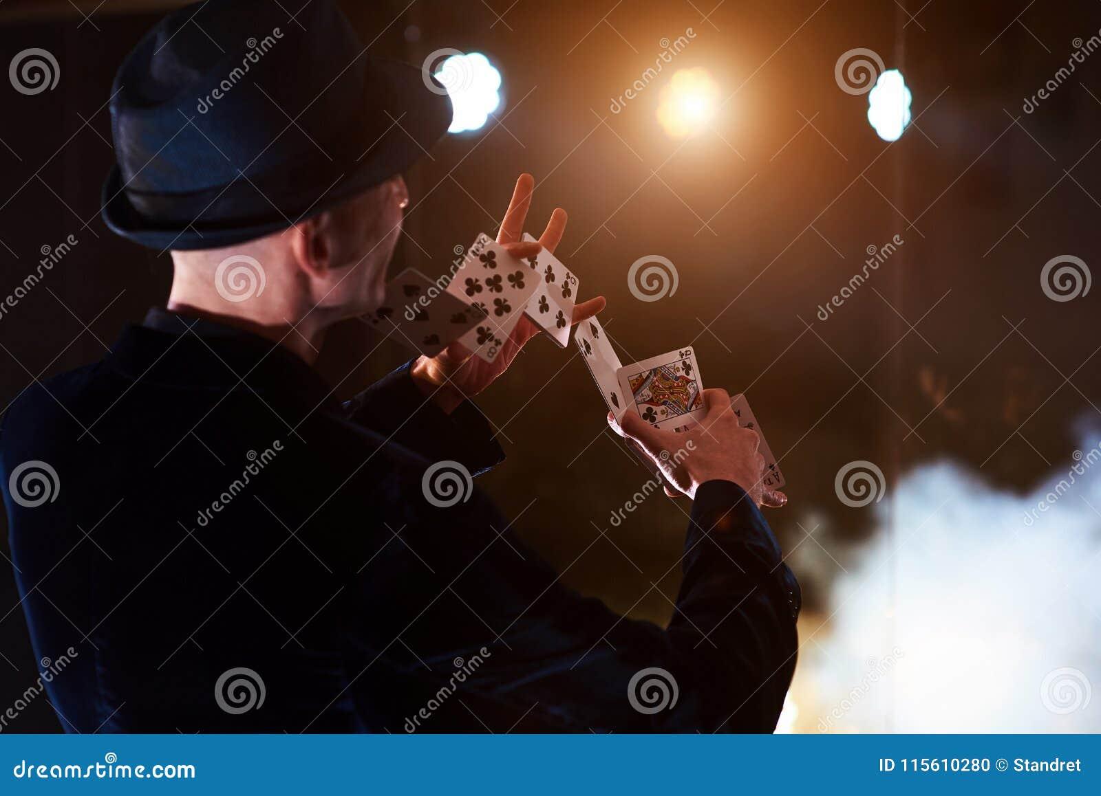 Tovenaar die truc met speelkaarten tonen Magisch of handigheid, circus, het gokken Goochelaar in donkere ruimte met mist