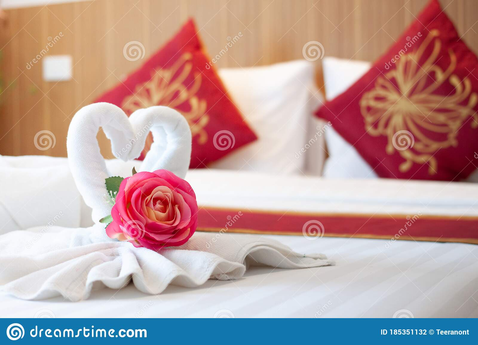 Towels Folded In Bird Shape With Pink Flowers On The White Bed In The Bedroom With Wood Headboard And Red Chinese Style Pillows Stock Photo Image Of Indoors Apartment 185351132