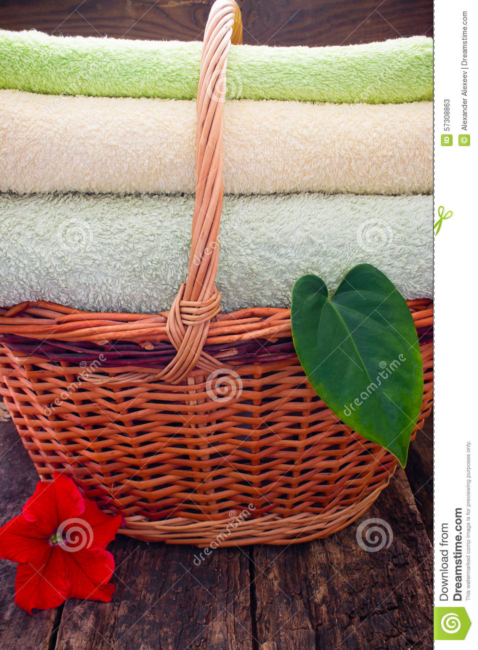 Next Woven Basket : Towels in a wicker basket next to the flowers and leaves