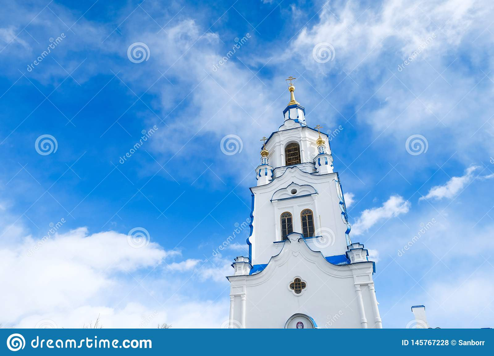 The tower of Church on background of blue sky with clouds. Russia, Tyumen