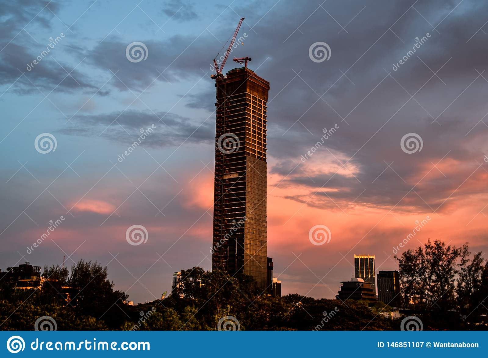 Tower crane on top of an unfinished building in the evening at Bangkok, Thailand