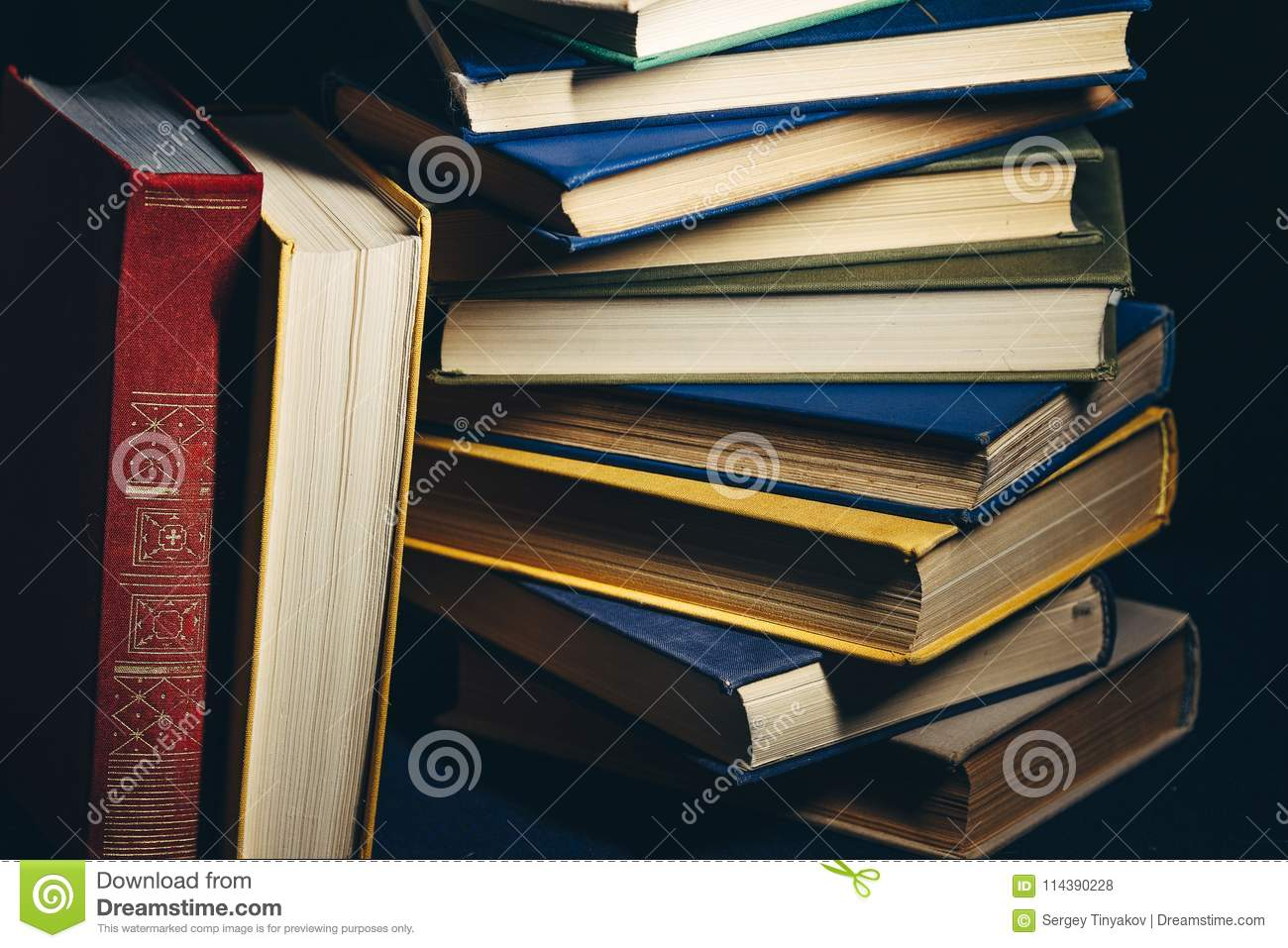 Tower Of Colorful Books On A Black Background. Concept Of Education And Knowledge