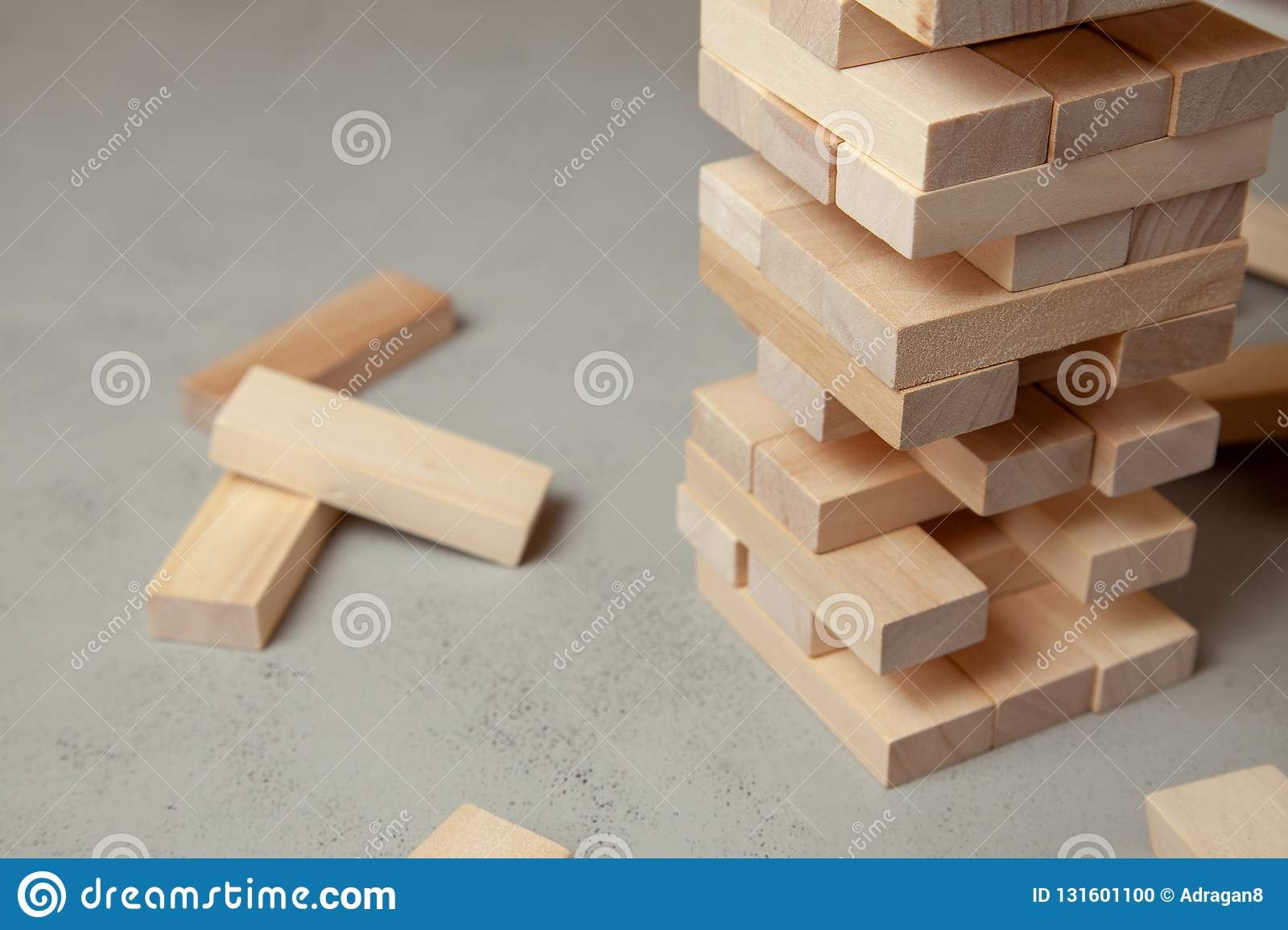 Tower of wooden blocks on gray background. Board game for the whole family or party. Concept of building business or building team