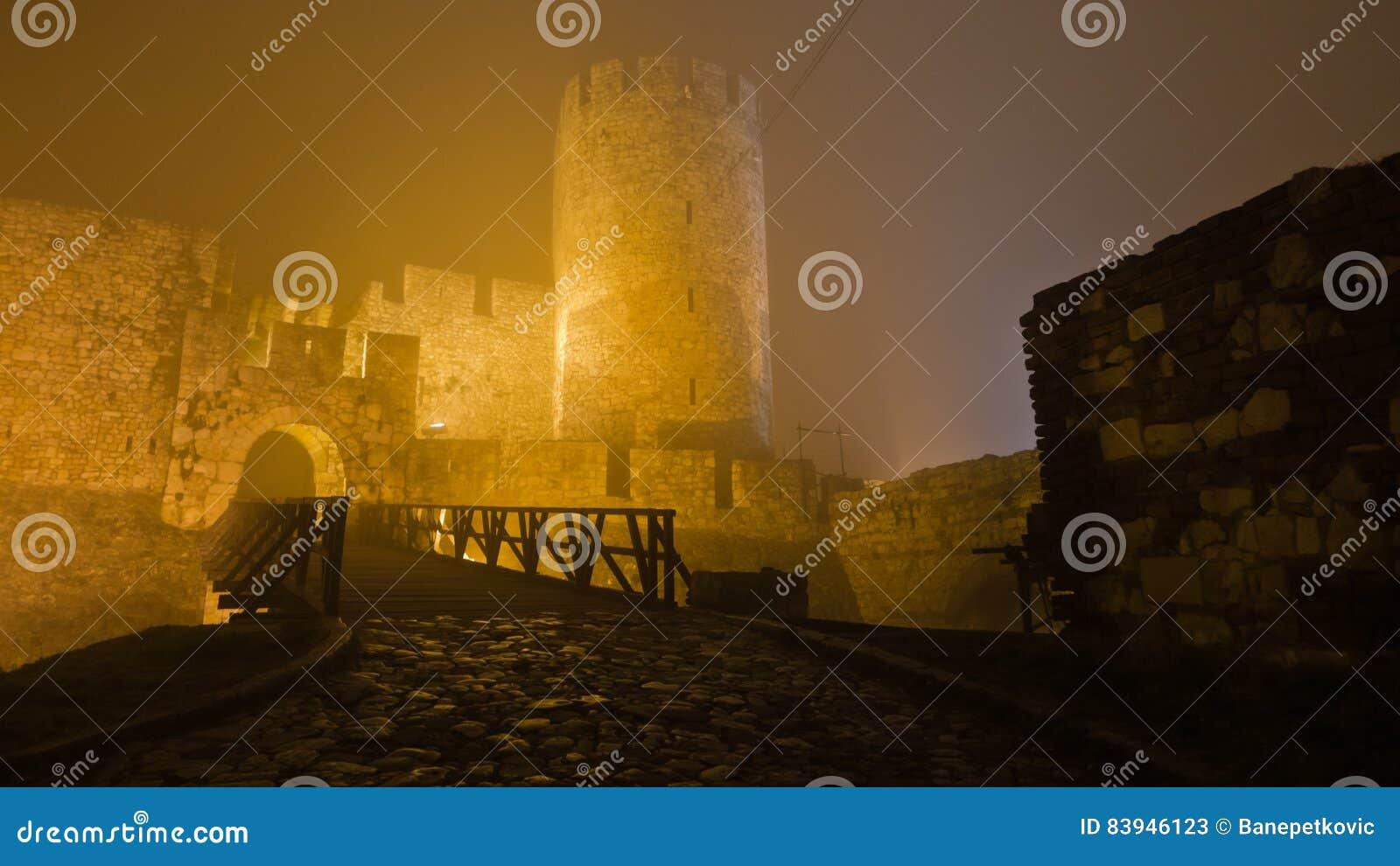 Tower and wooden bridge of Kalemegdan fortress at foggy night in Belgrade