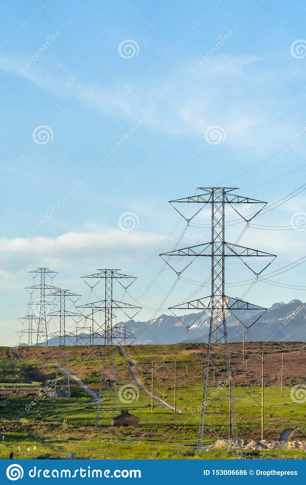 Towering power lines in the valley against snow capped mountain and blue sky