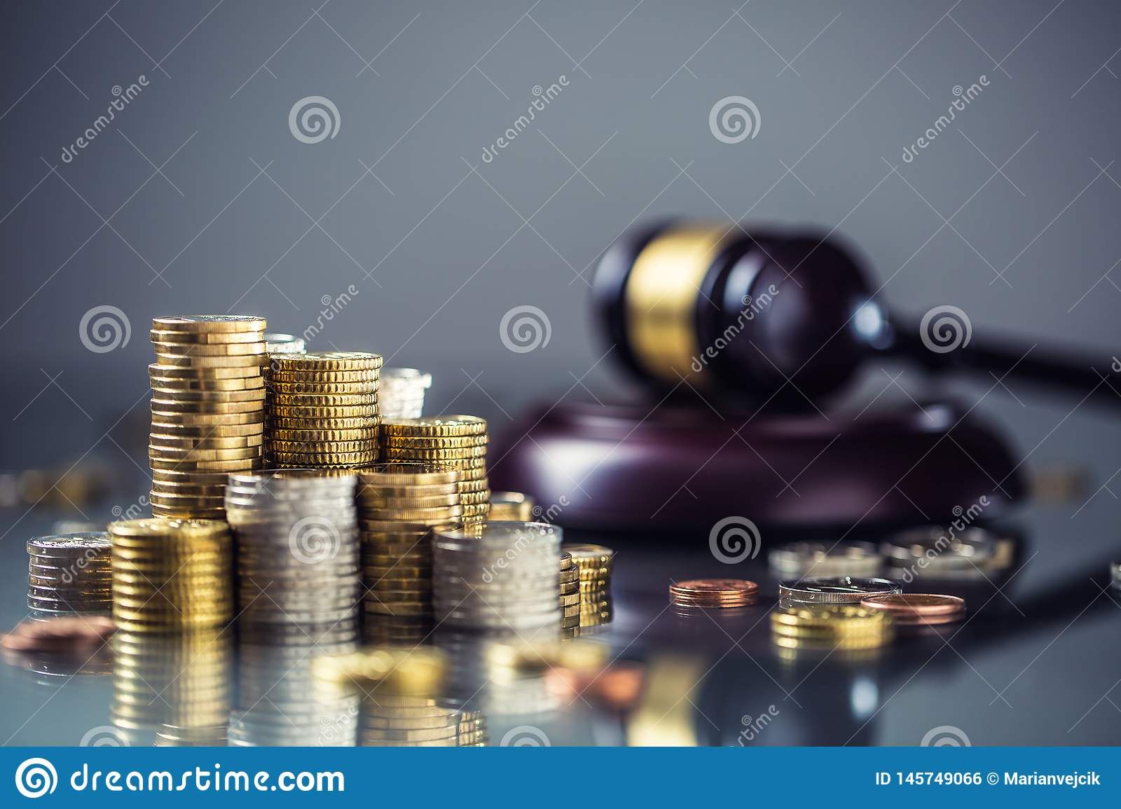 Towers with euro coins and justice hammer in the background
