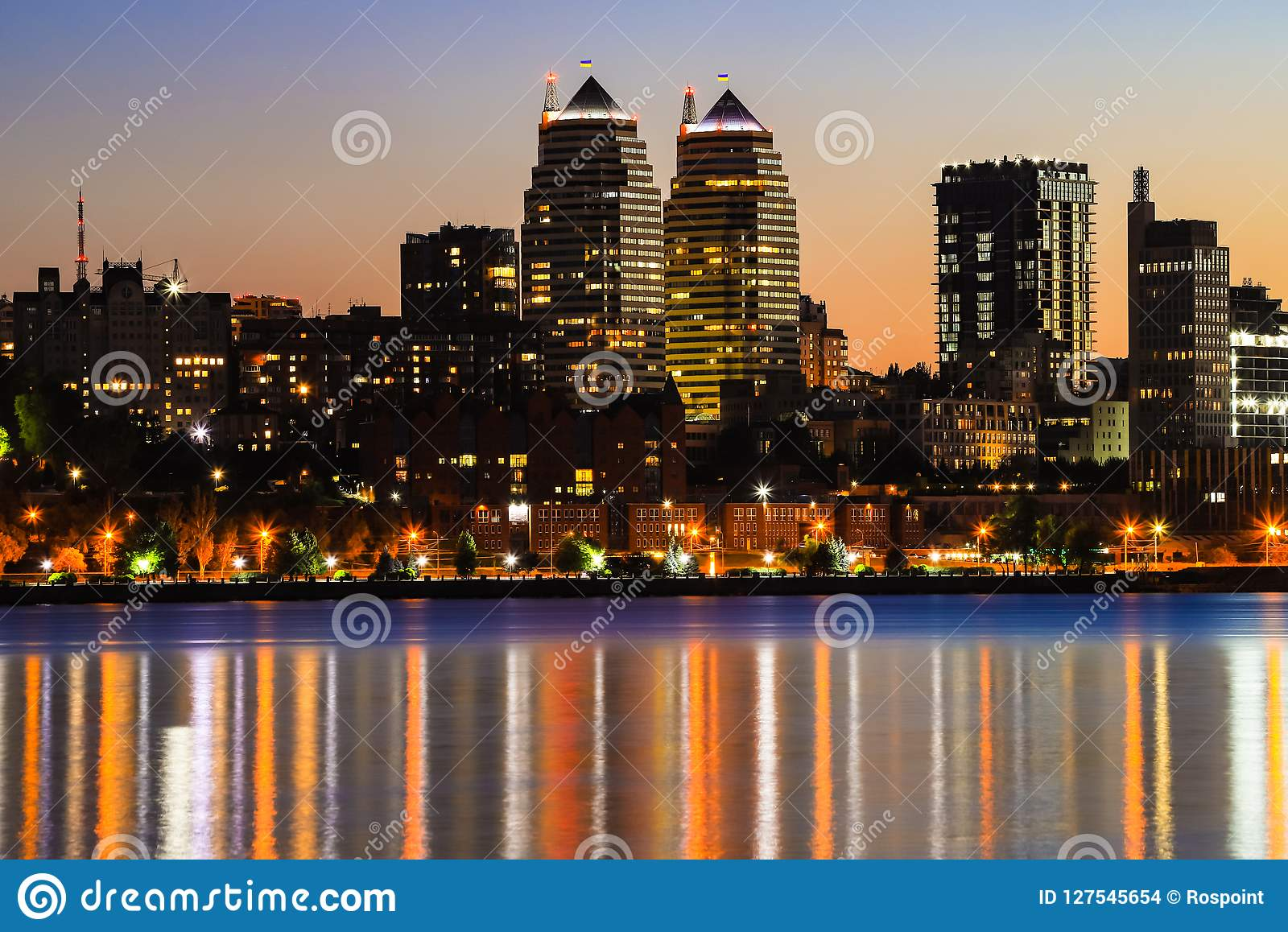 Towers, skyscrapers and buildings in Dnepr city at night, lights reflected on the river Dnieper, Ukraine.
