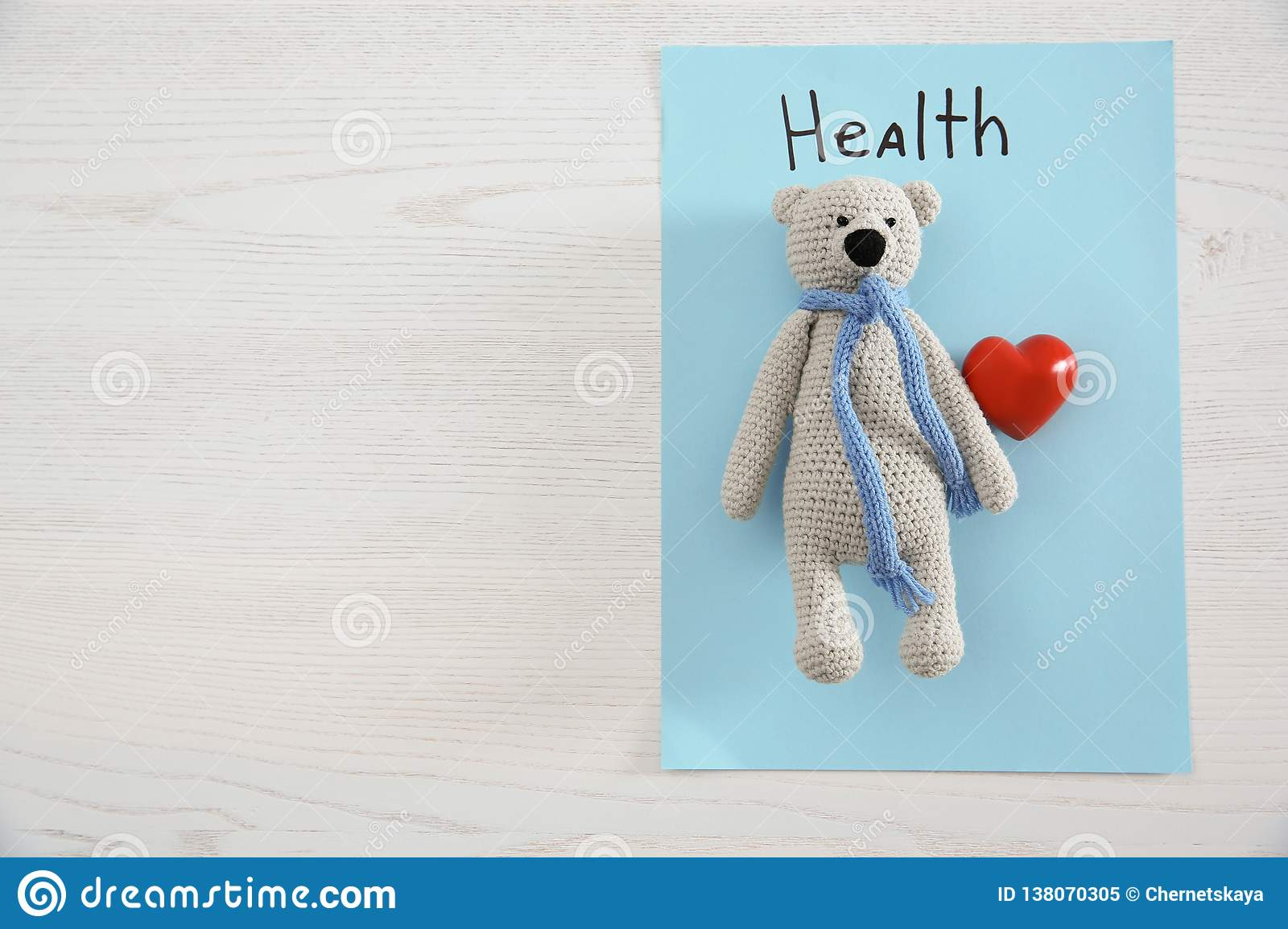 Toy bear, heart, sheet of paper with word HEALTH and space for text on wooden background, top view.