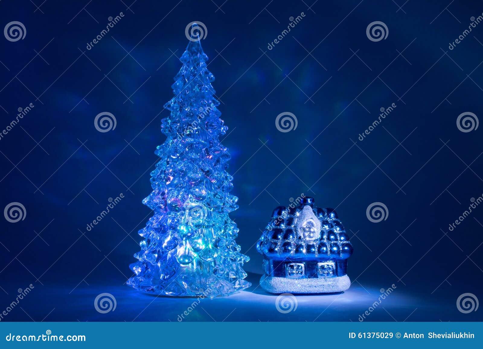 Toy Christmas-boom die met mooie schaduwen Noordelijke Lichten dichtbij het huis van een sprookje op een donkerblauwe achtergrond