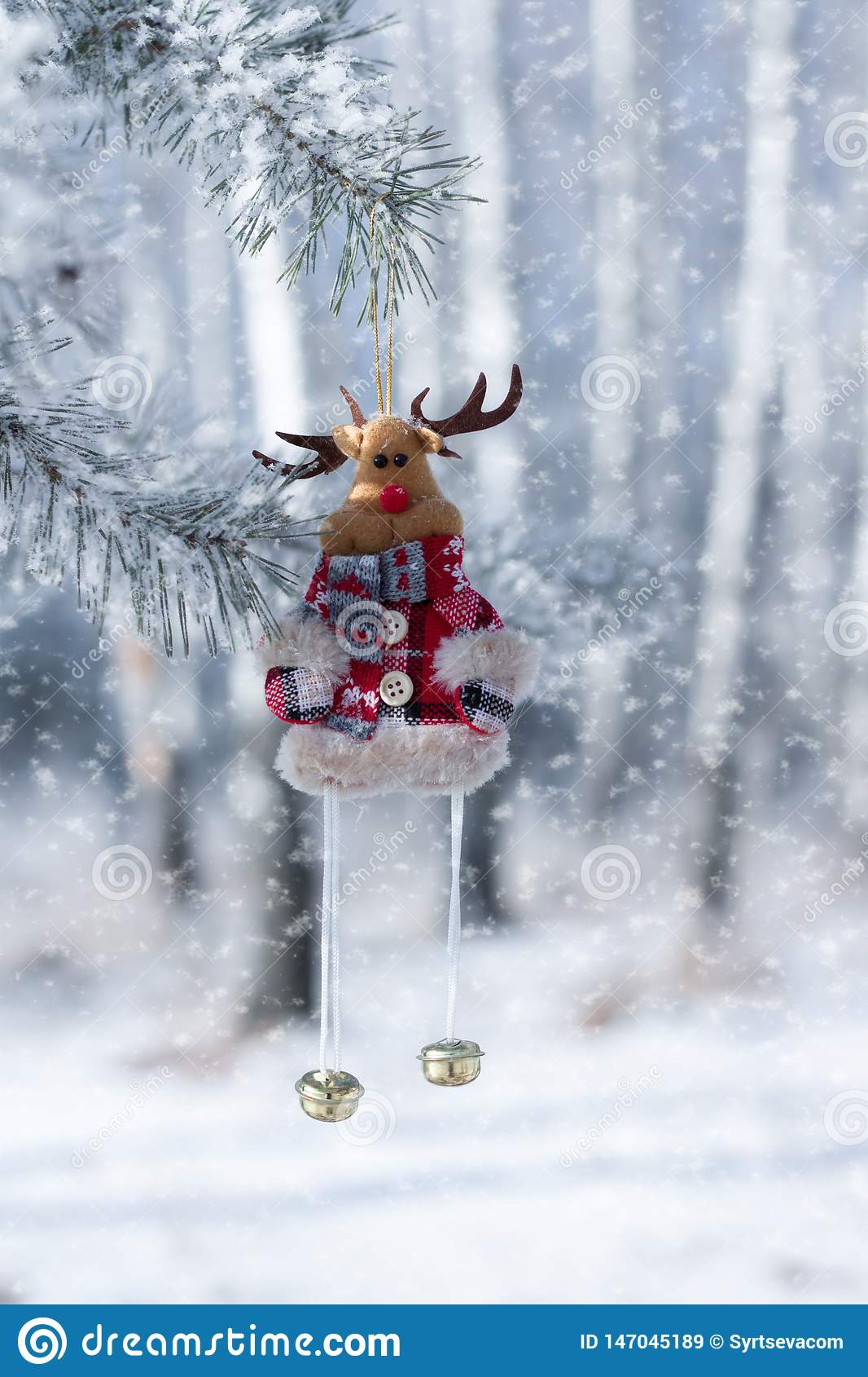 Toy deer with bells, Christmas decoration, close-up, against the winter forest, where snow falls