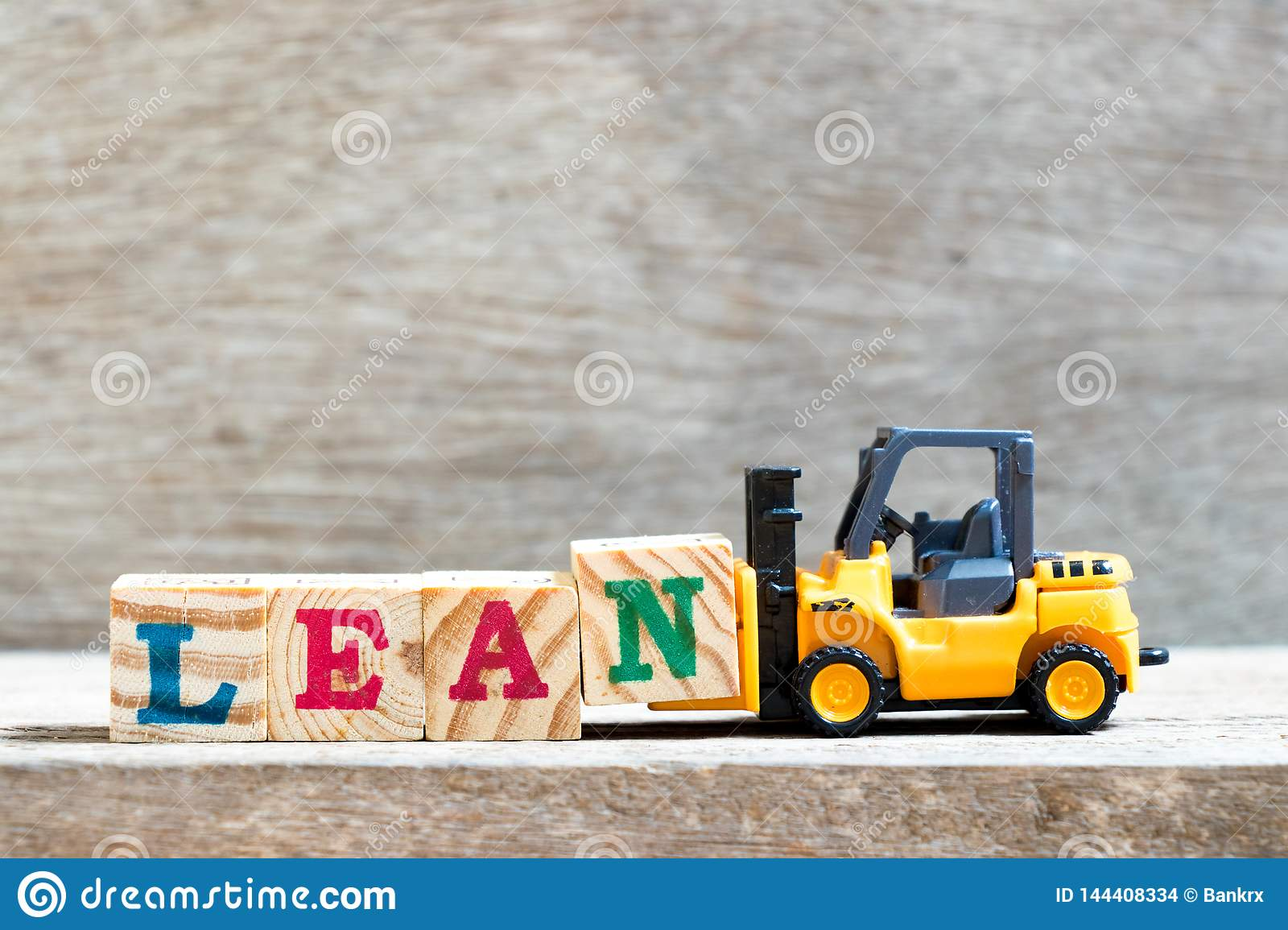 Toy forklift hold letter block n to word lean on wood background